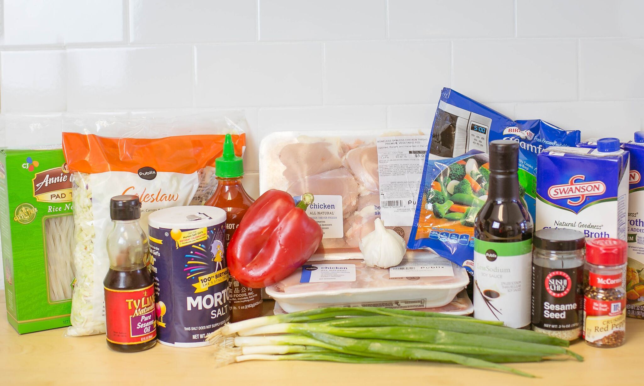 Assemble your ingredients: Chicken thighs, frozen vegetables, soy sauce, garlic, green onions, red bell pepper, chicken stock, rice noodles, shredded slaw mix, sesame seeds, spicy sauce, sesame oil, red pepper flakes and sriracha sauce.