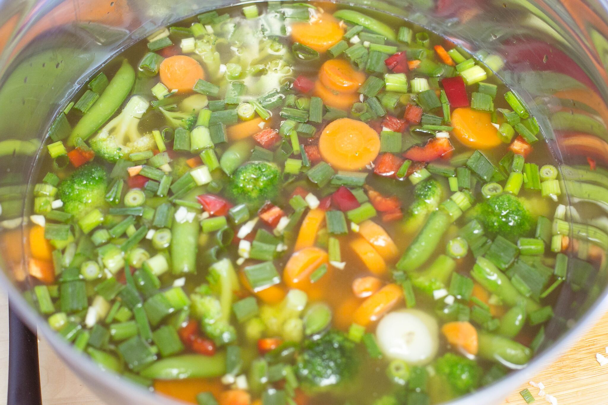 In a large bowl mix together stock, green onions, red pepper, garlic, frozen vegetables and soy sauce.