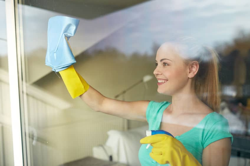 A woman cleaning windows with spray, rubber gloves and a rag.