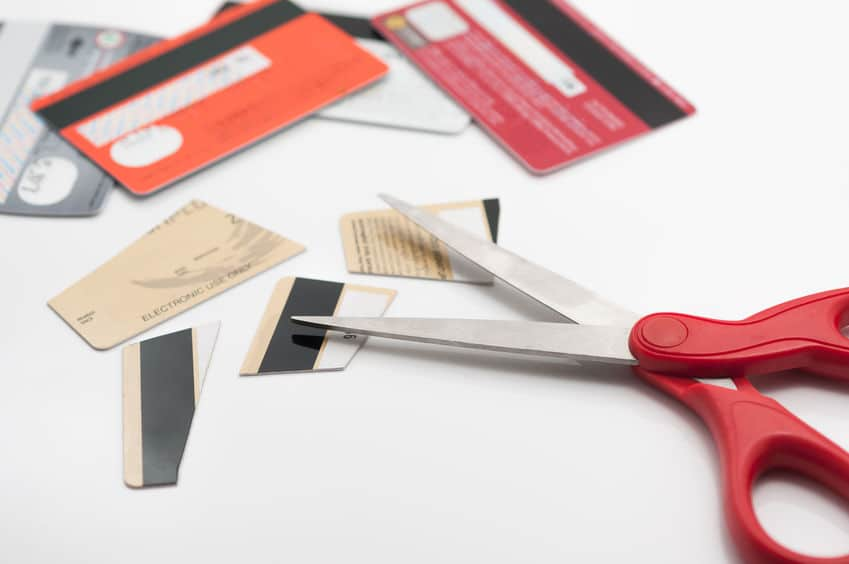 Cutting credit cards into pieces.