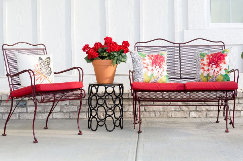 Colorful and floral outside patio furniture decorated with red accents.