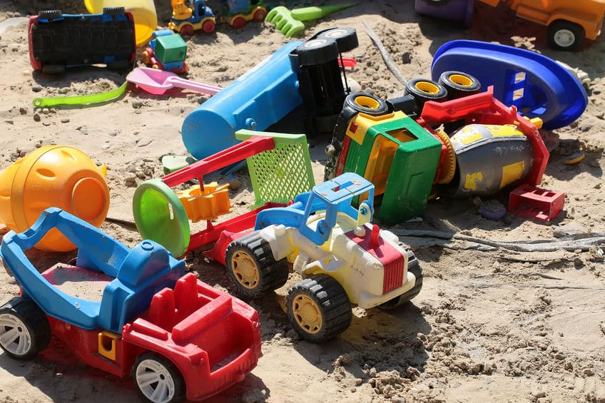 A pile of beach toys in the sand.