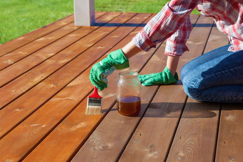 Using rubber gloves, a mason jar and a paint brush, apply protective sealant to the wooden deck.
