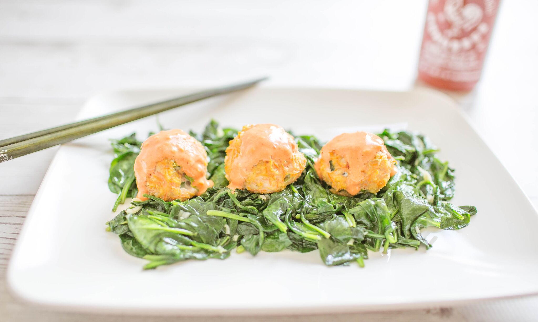 Serve chicken meatballs with sriracha sauce over a fresh greens.