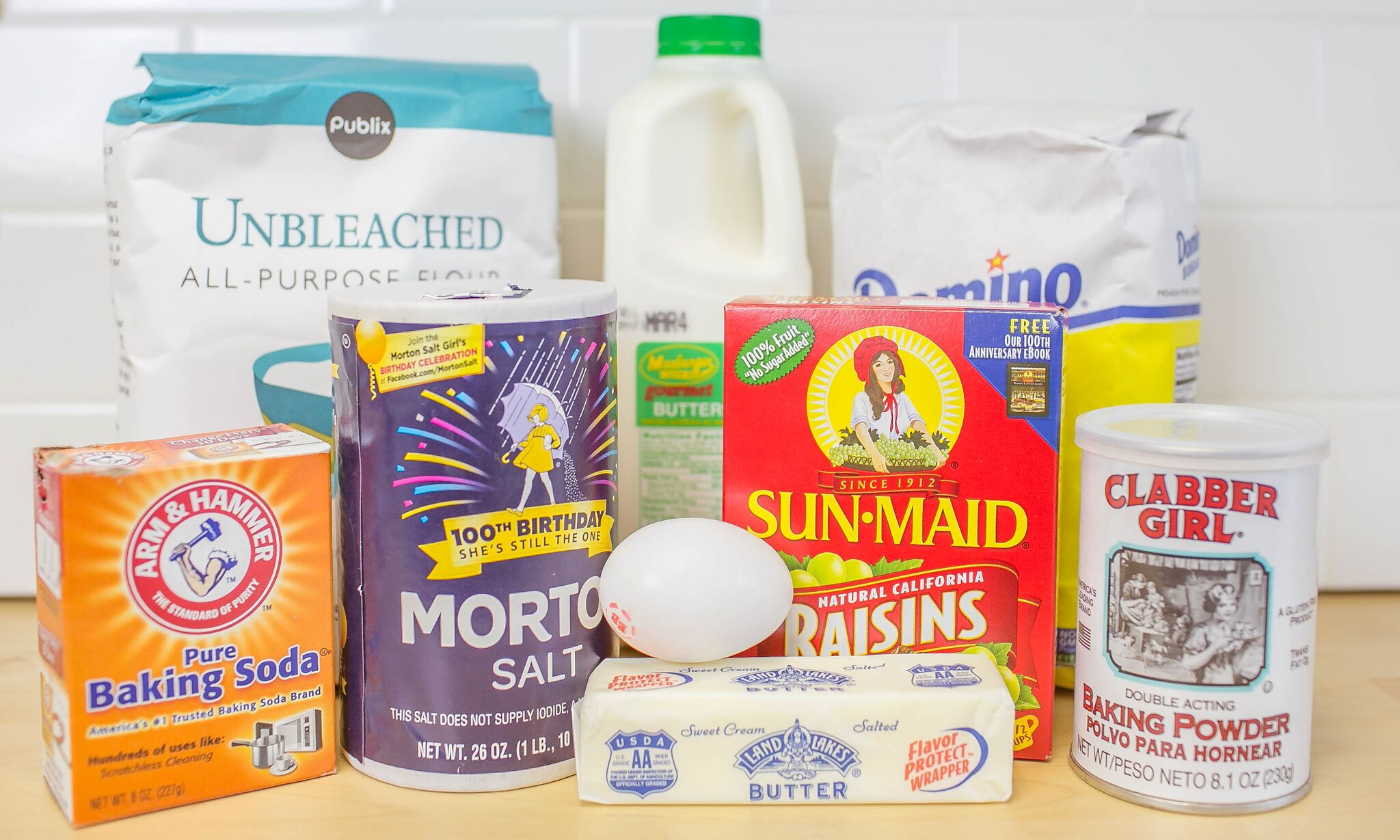 Ready to make Irish soda bread? Here are the ingredients: flour, buttermilk, sugar, salt, raisins, eggs, butter, baking powder and soda.