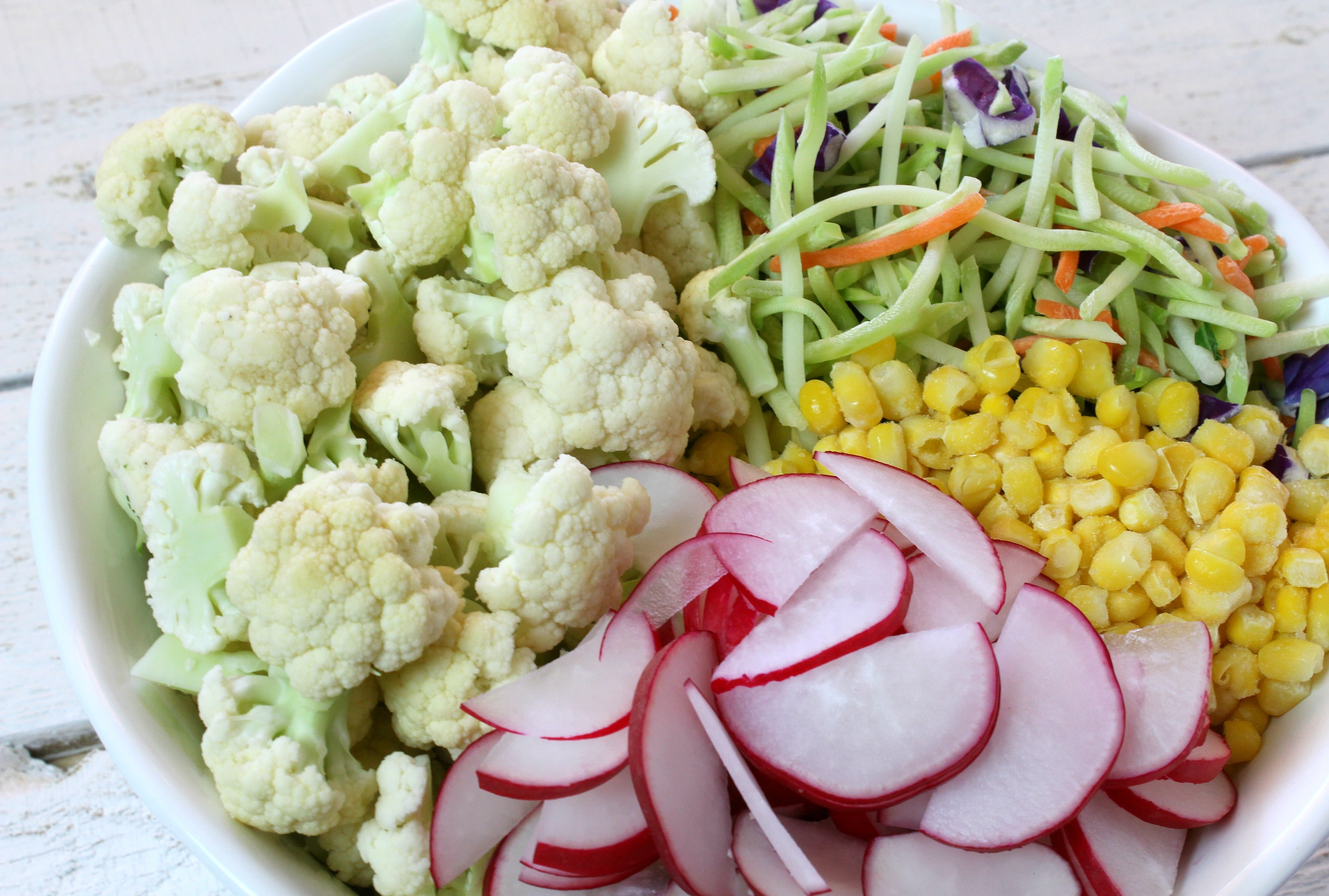 Place all broccoli slaw, cauliflower, corn, and radish in a large bowl.