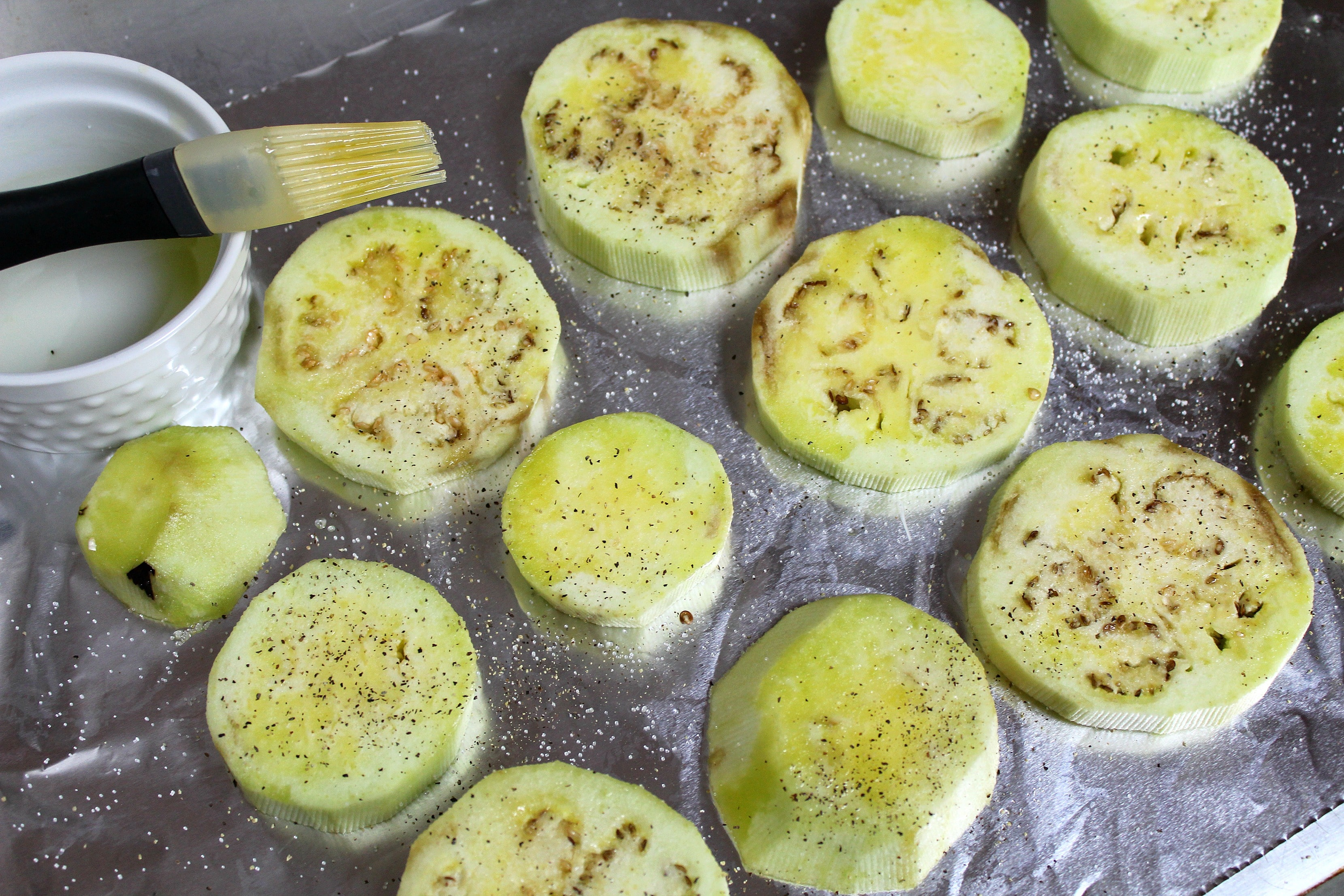PLace eggplant slices on baking sheet. Brush with olive oil and sprinkle with salt and pepper.