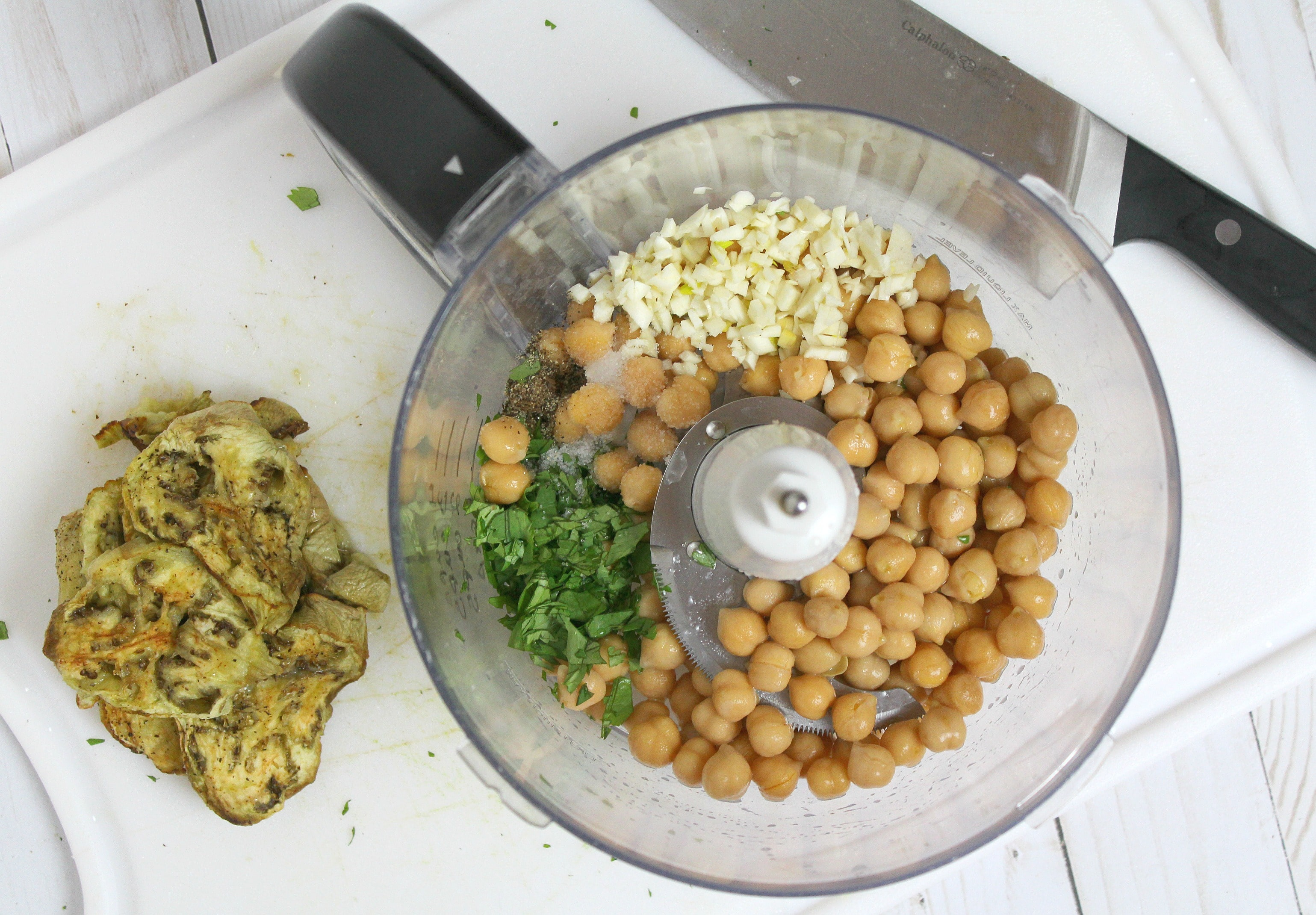 Add chickpeas, garlic, and other ingredients to a food processor and blend for a few seconds, until smooth.