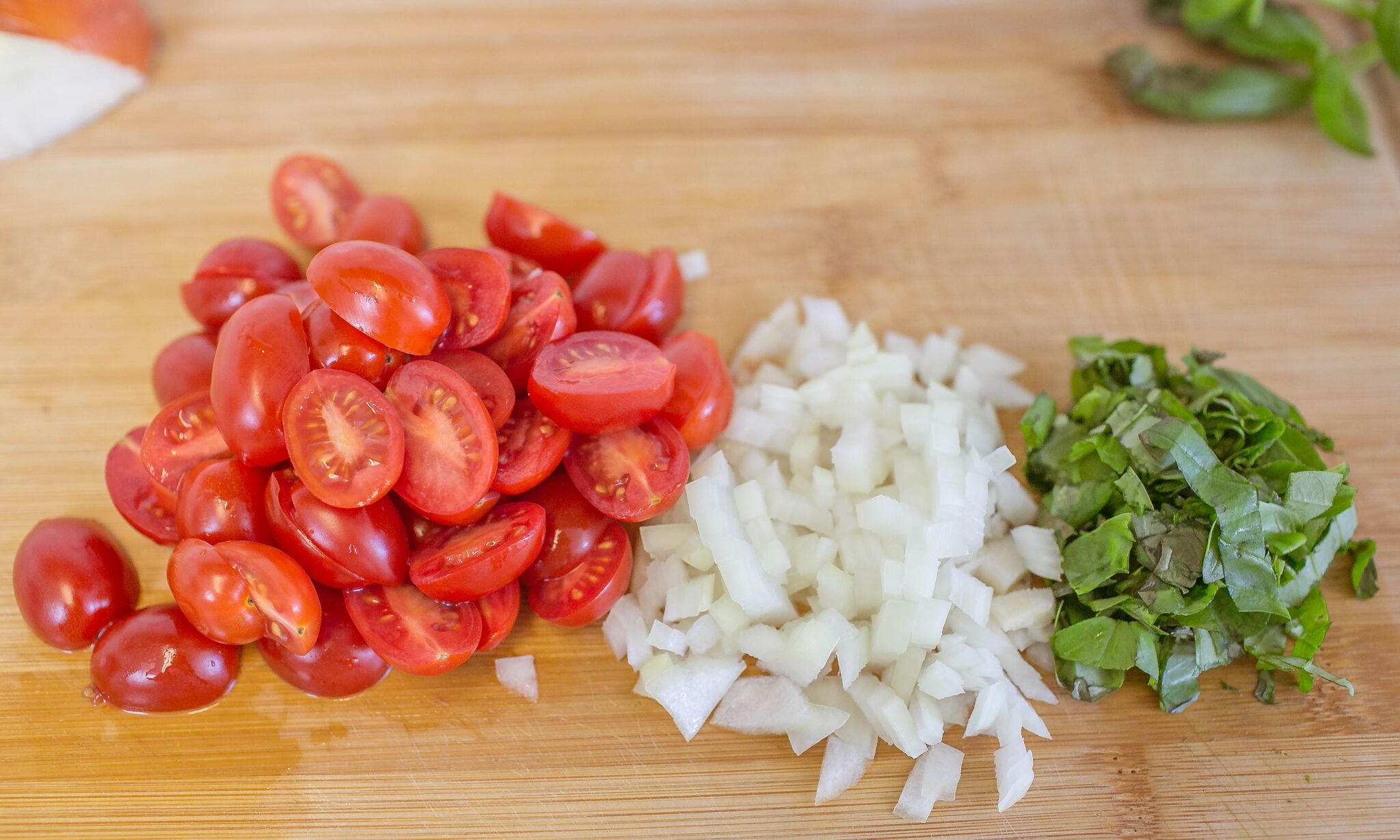 Dice onion, slice tomatoes, and chop basil then set aside.