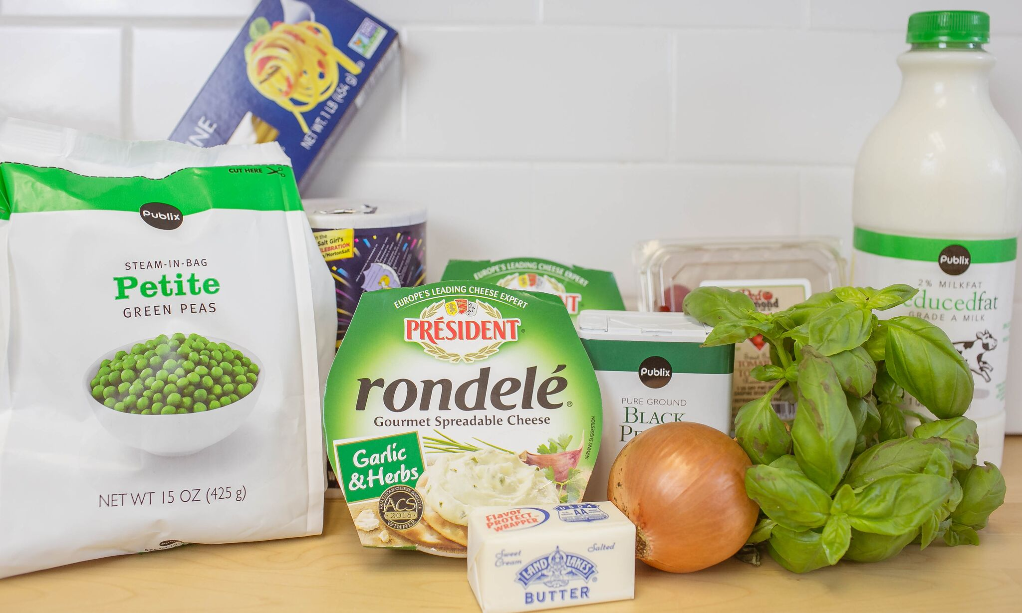 Assemble your ingredients for the pasta: basil, tomatoes, boxed pasta, milk, garlic and herb spreadable cheese, peas, onion, salt, pepper and butter.
