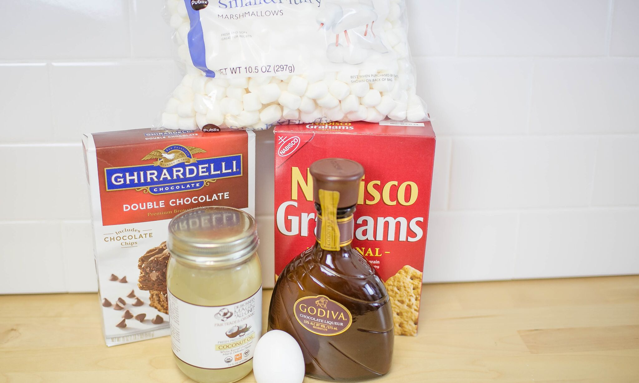 Assemble your ingredients for the brownie s'mores: brownie mix, one egg, Godiva liquor, coconut oil, mini marshmallows, and graham crackers.