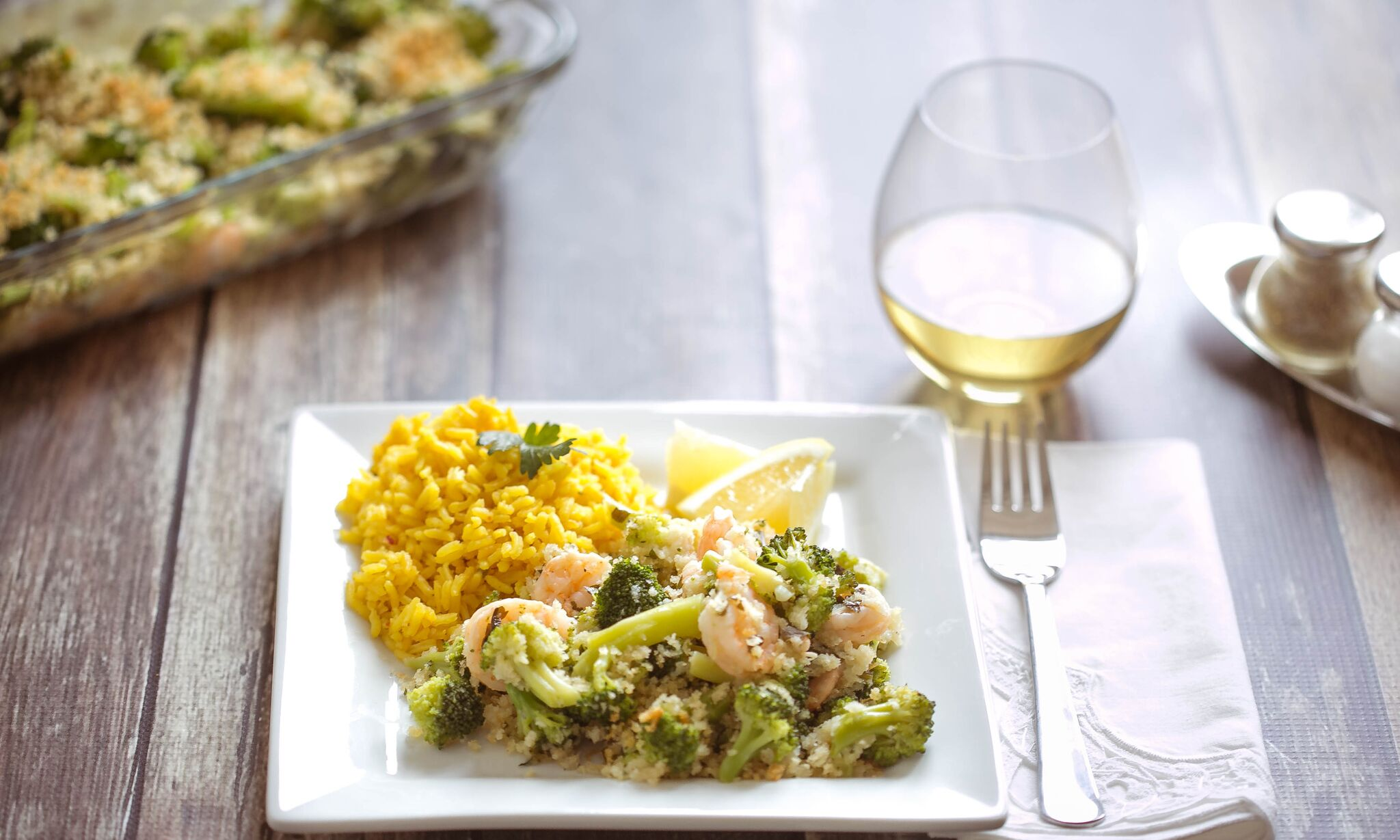 Serve finished shrimp and broccoli bake on plate with rice and a glass of wine