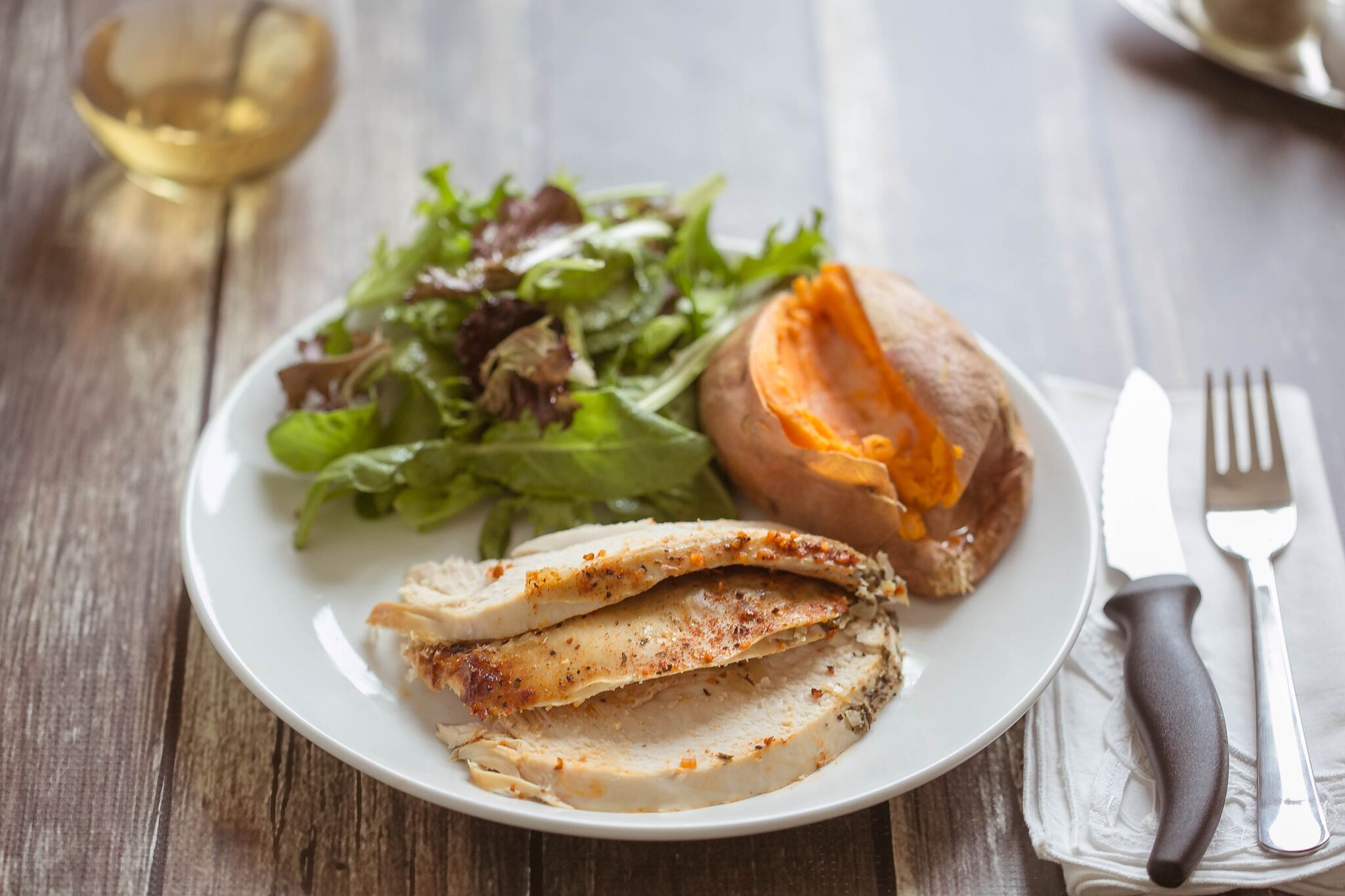 Serve finished chicken with a salad, sweet potato, and a glass of wine then enjoy.