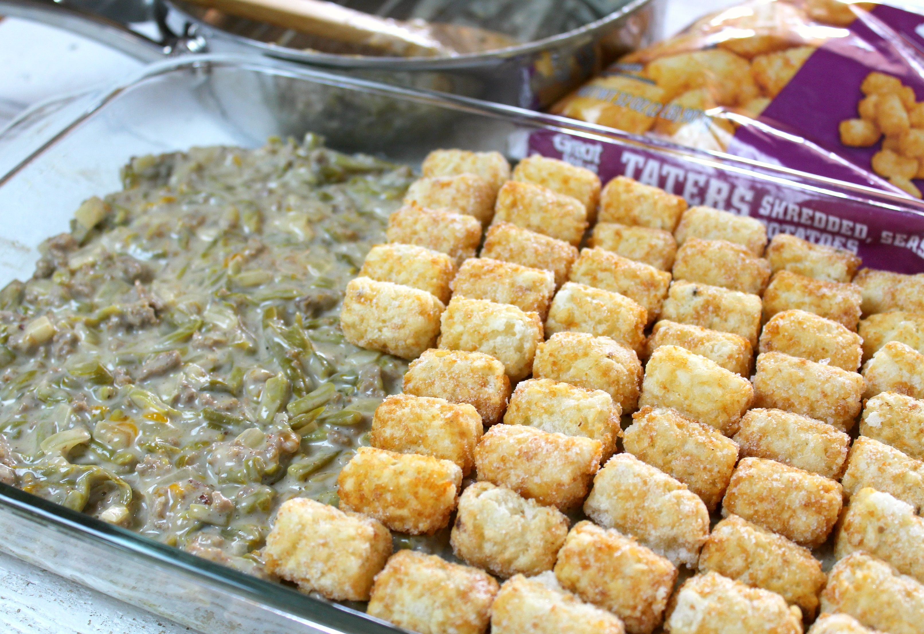 Tater Tot Casserole | Pour mixture into the 9x13 pan and top with a layer of frozen tater tots.