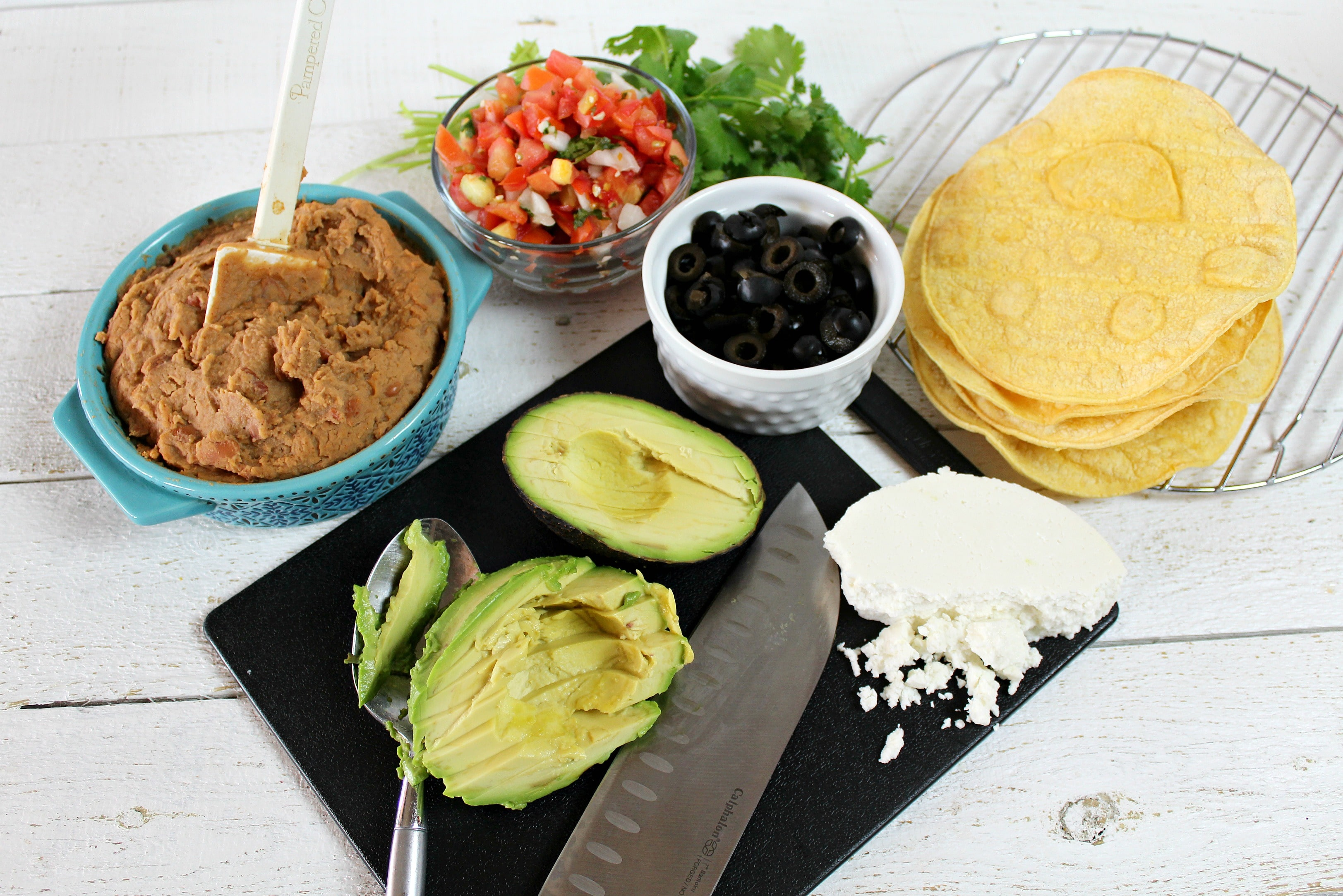 Slice the avocado and assemble the ingredients including the beans, salsa, cilantro, olives and of course, the tortillas.