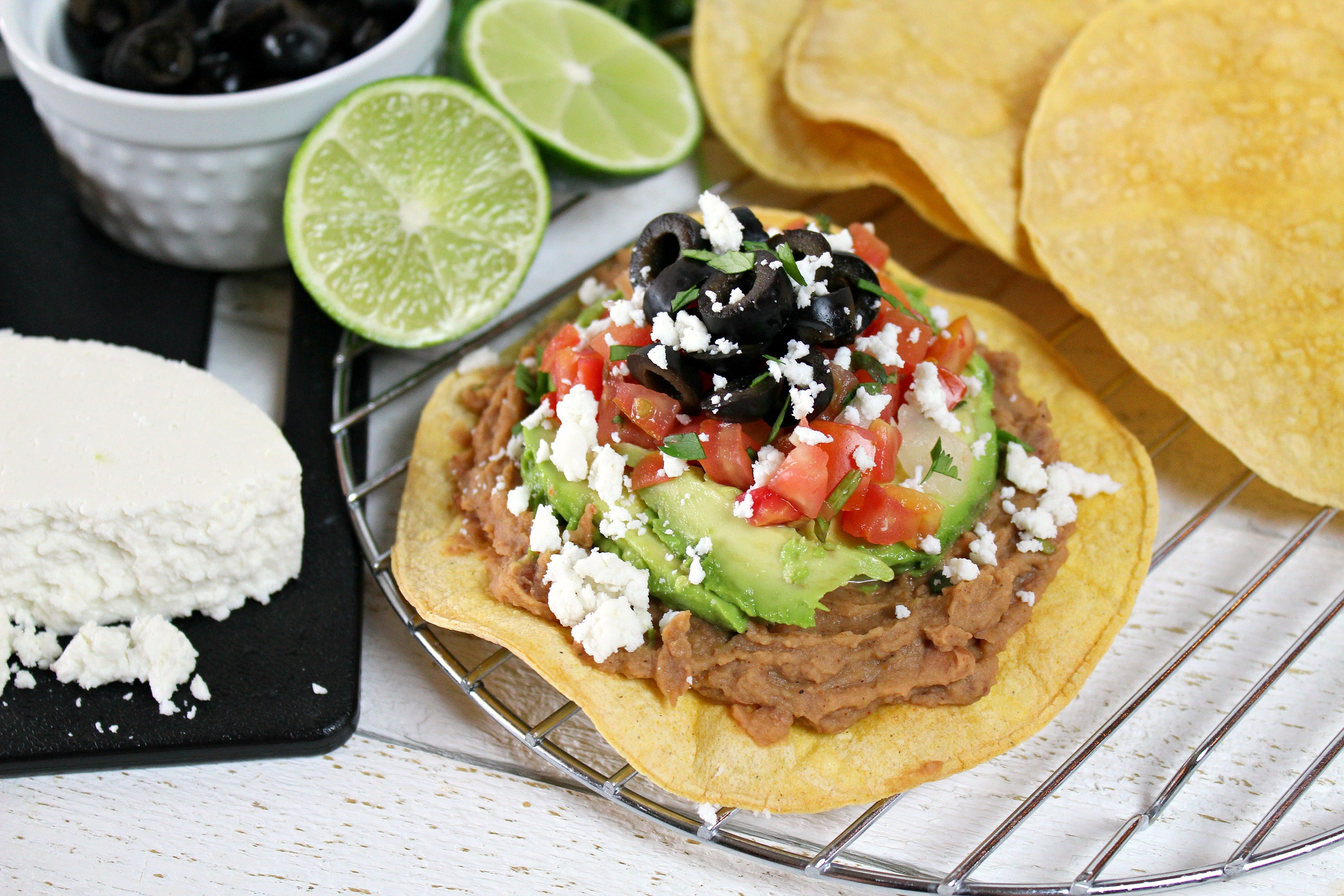 Assemble the easy, healthy vegetarian tostadas by topping them with the beans, vegetables and queso fresco.
