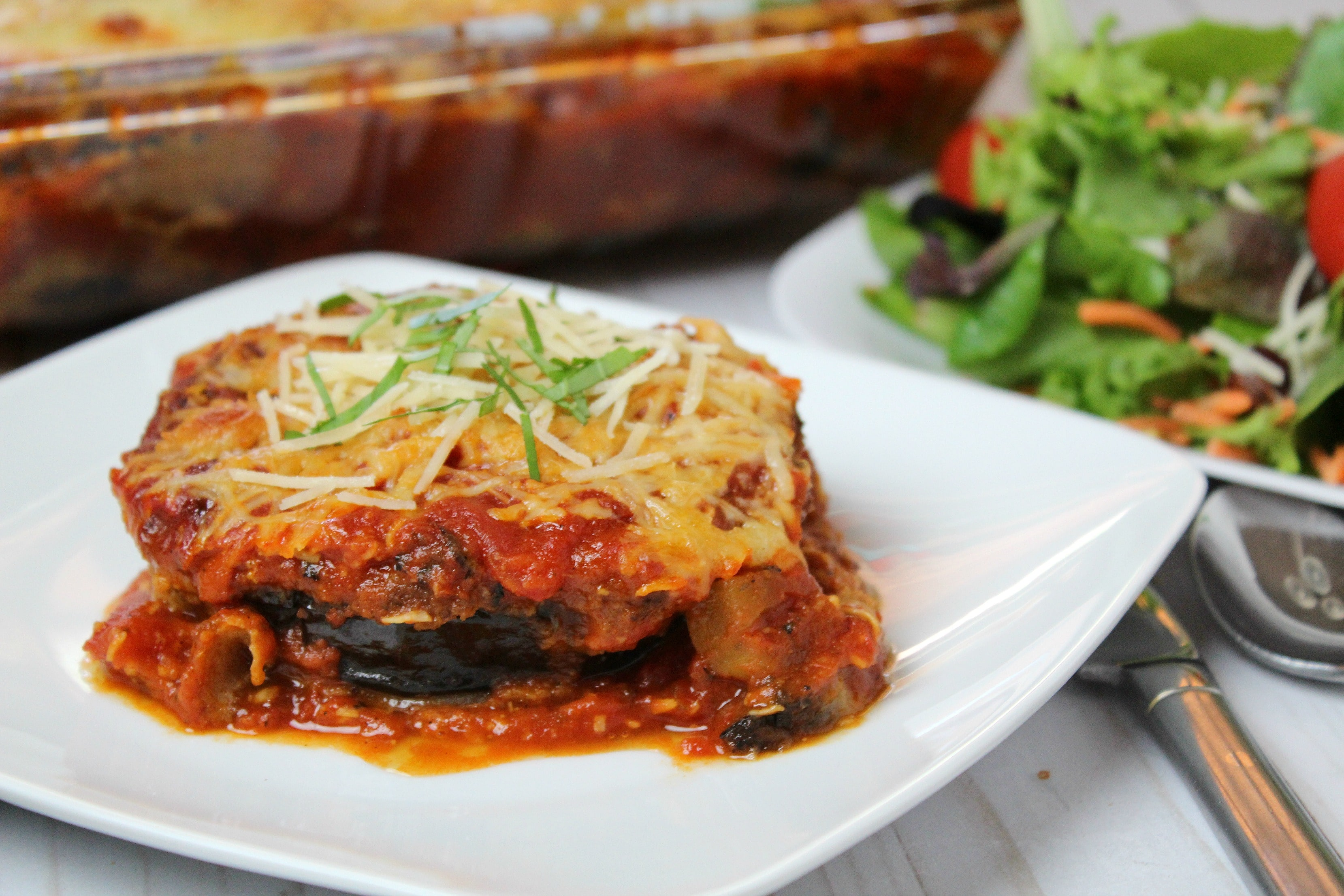 Serve finished eggplant Parmesan in plate with garnish.