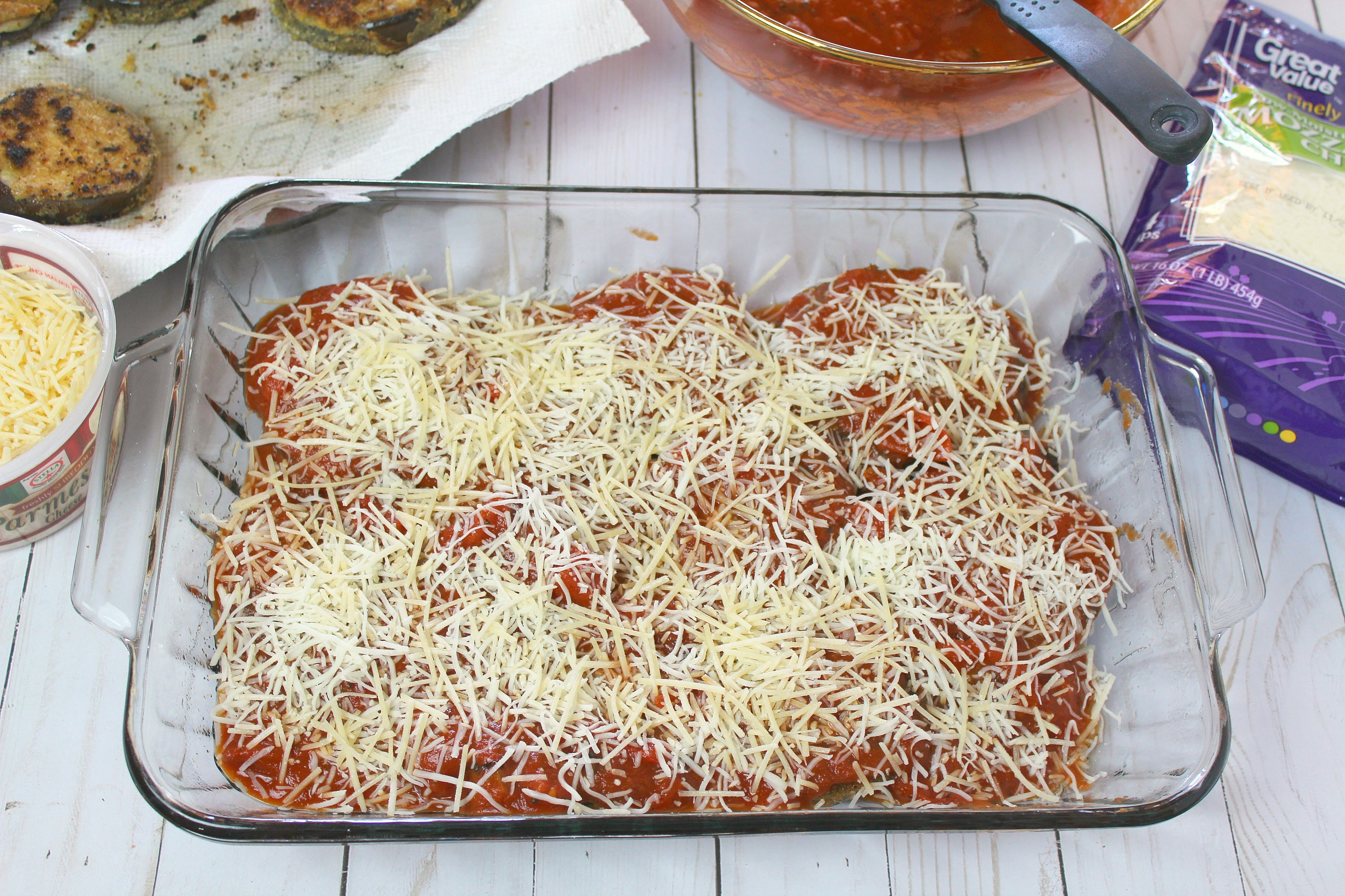 Layer eggplant over with sauce and cheeses in baking dish.