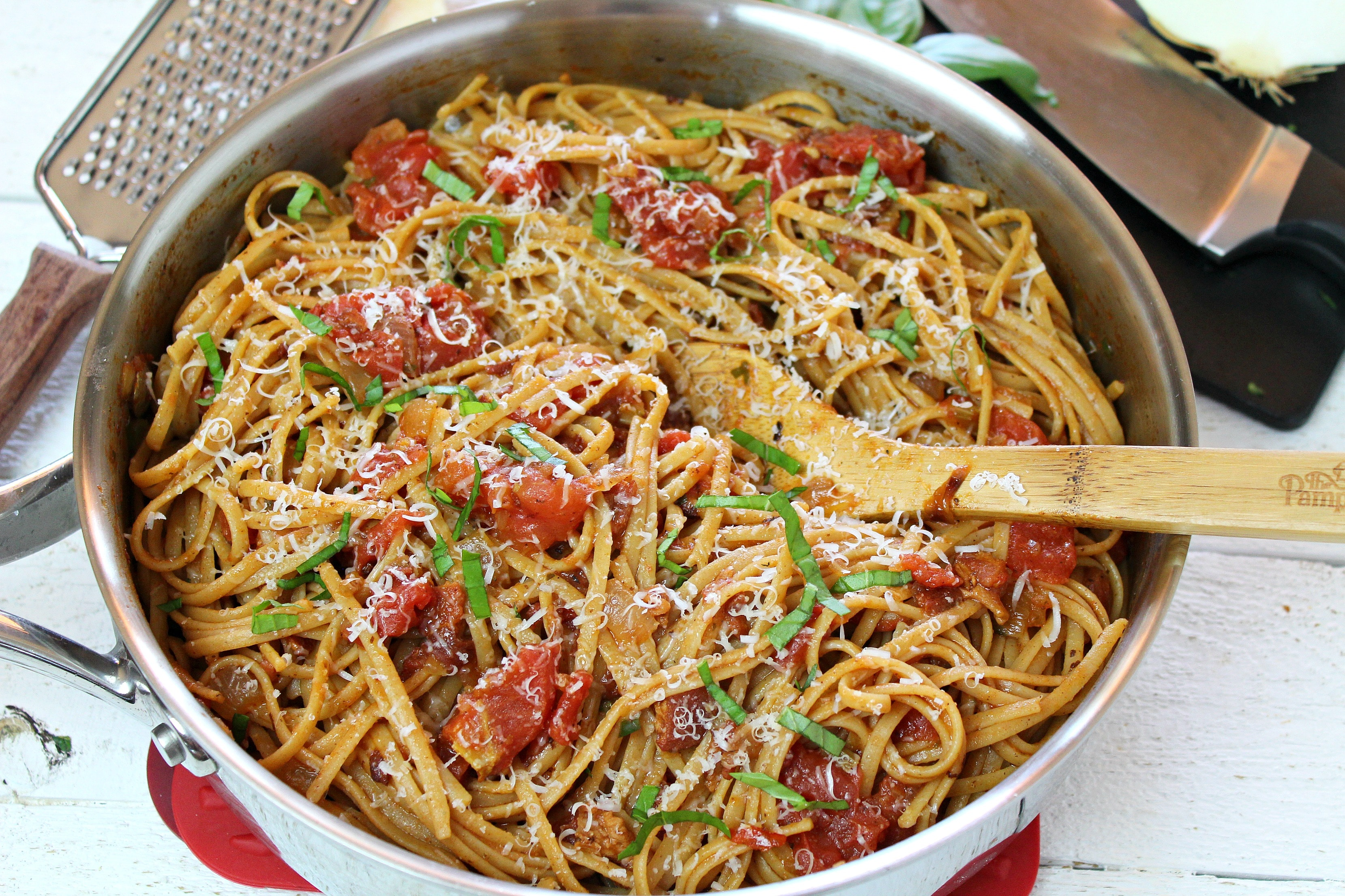 Serve linguine amatriciana topped with parmesan cheese and some chopped basil for a delicious homemade dinner