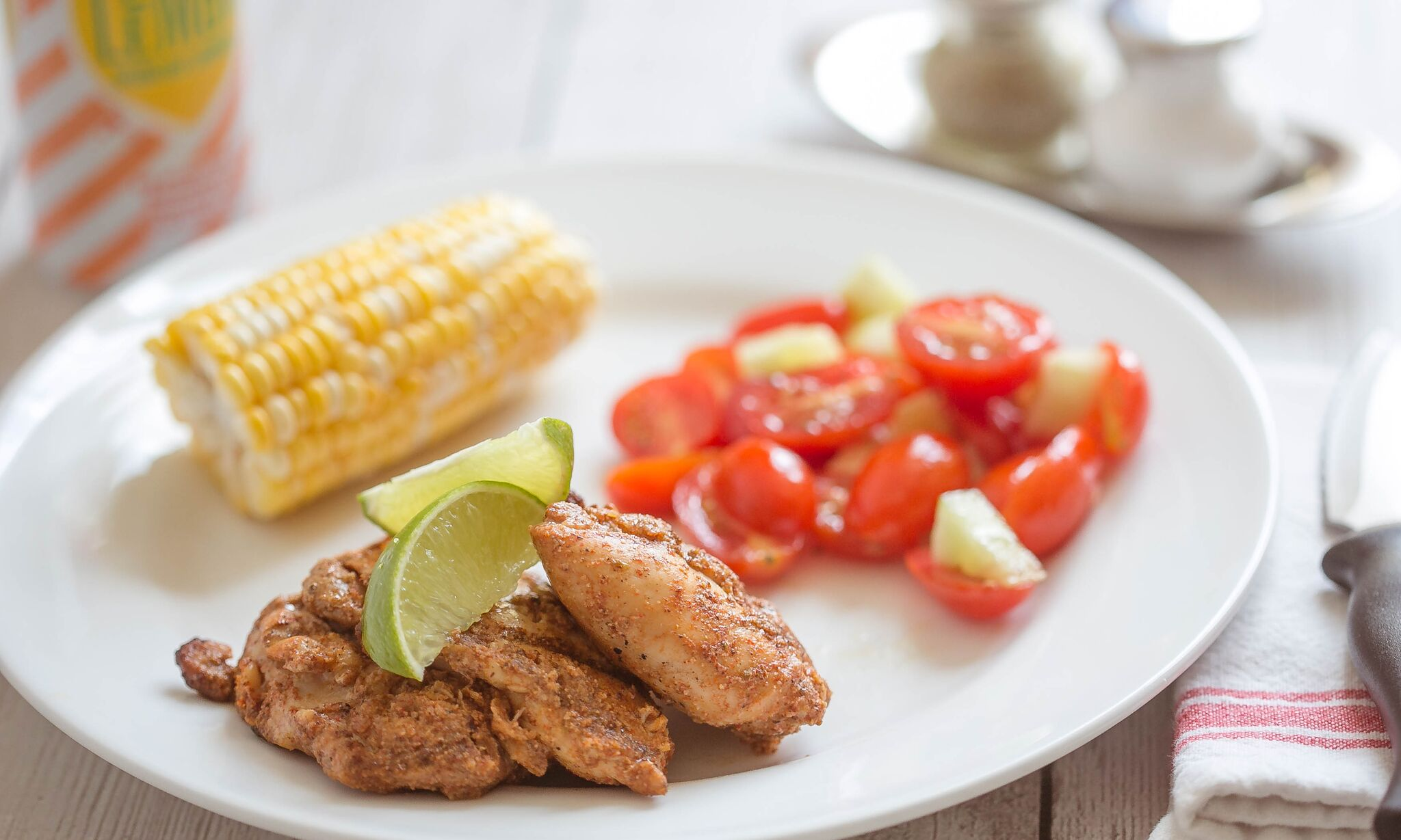 Serve grilled chicken with fresh lime and vegetables.