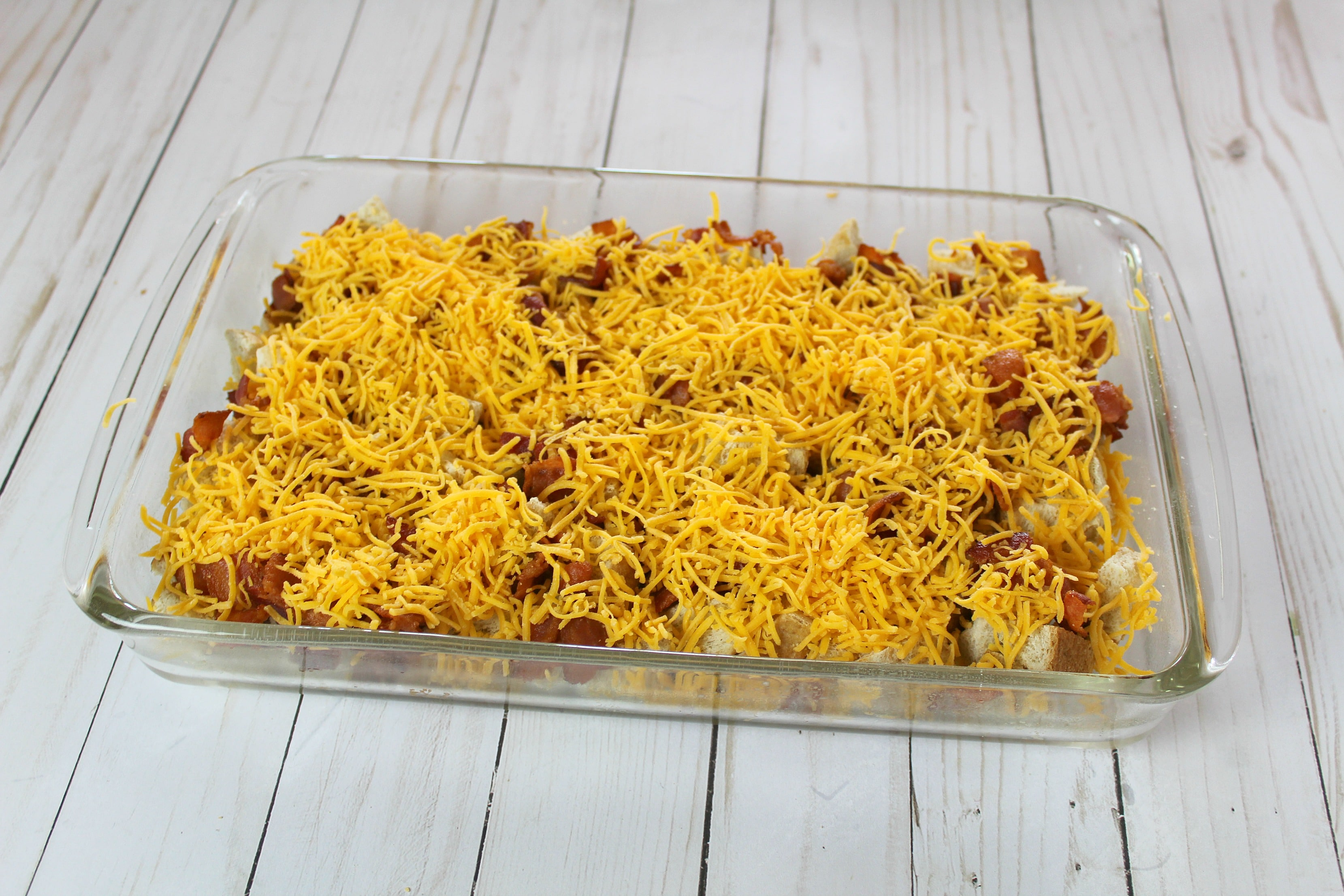 Add layer of meat, like sausage or bacon, and cheese over bread.