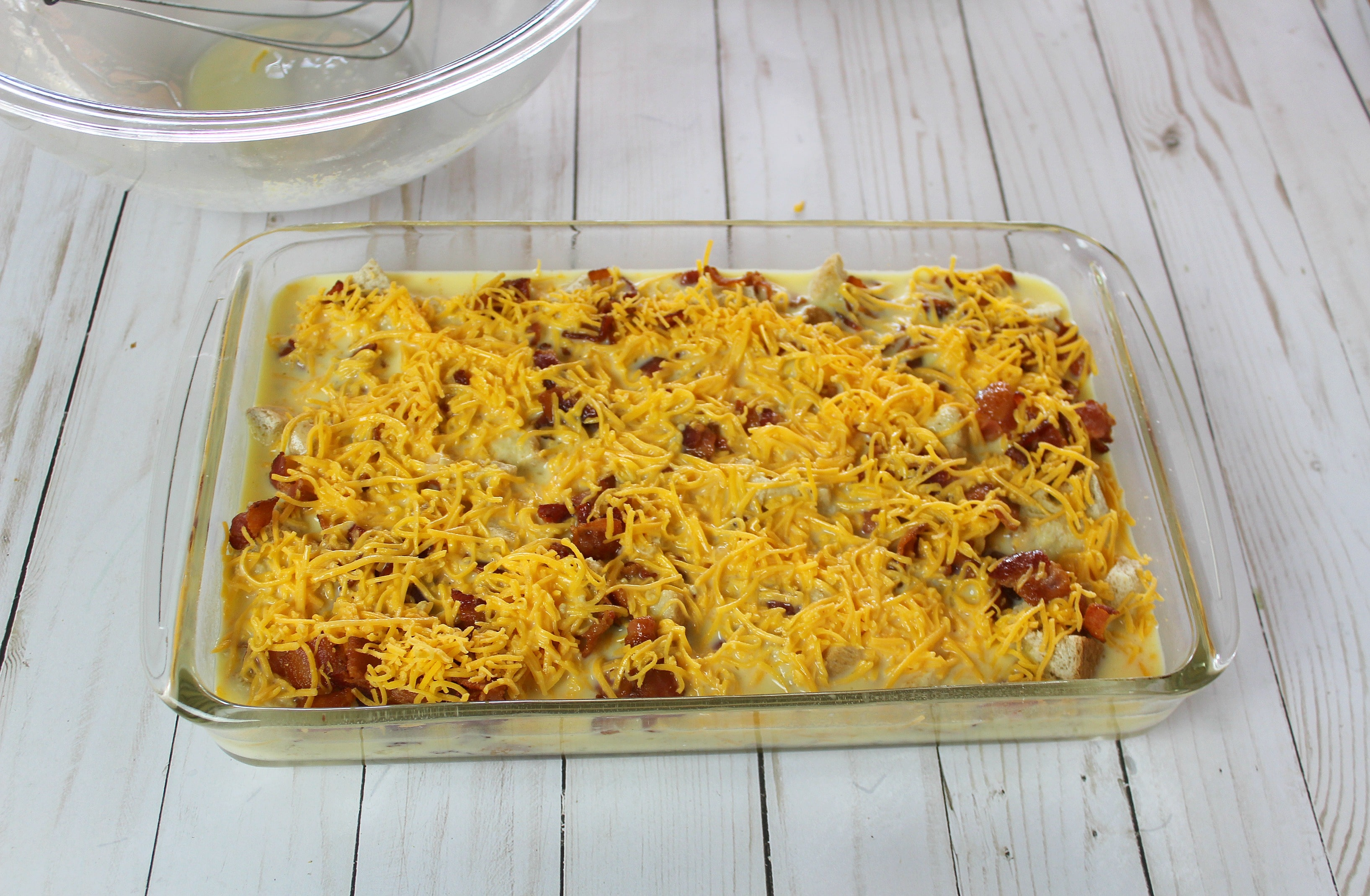 Pour egg mixture into casserole dish over bread, meat and cheese.