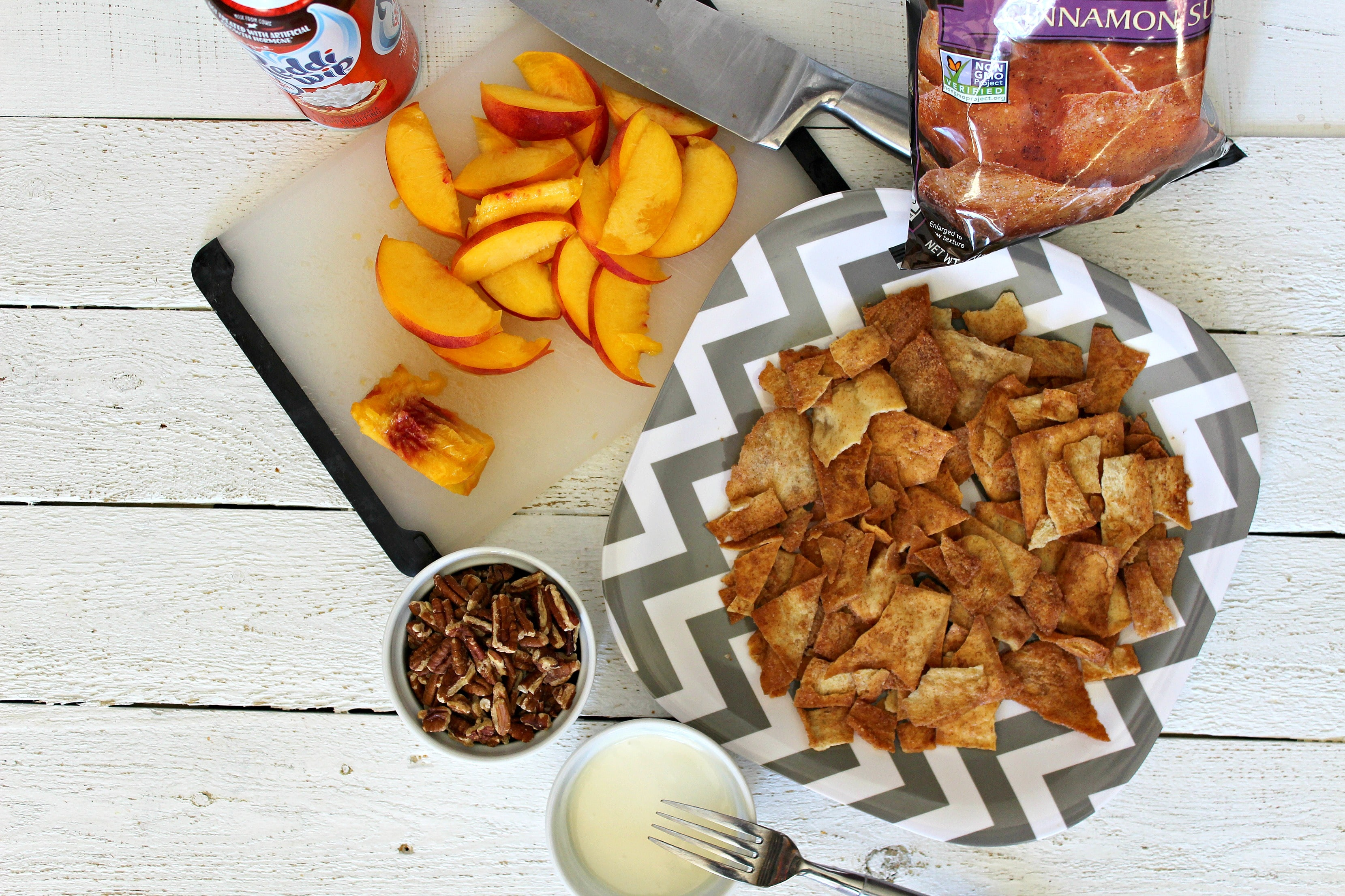 On a large plate layer cinnamon pita chips next to peaches and other ingredients.