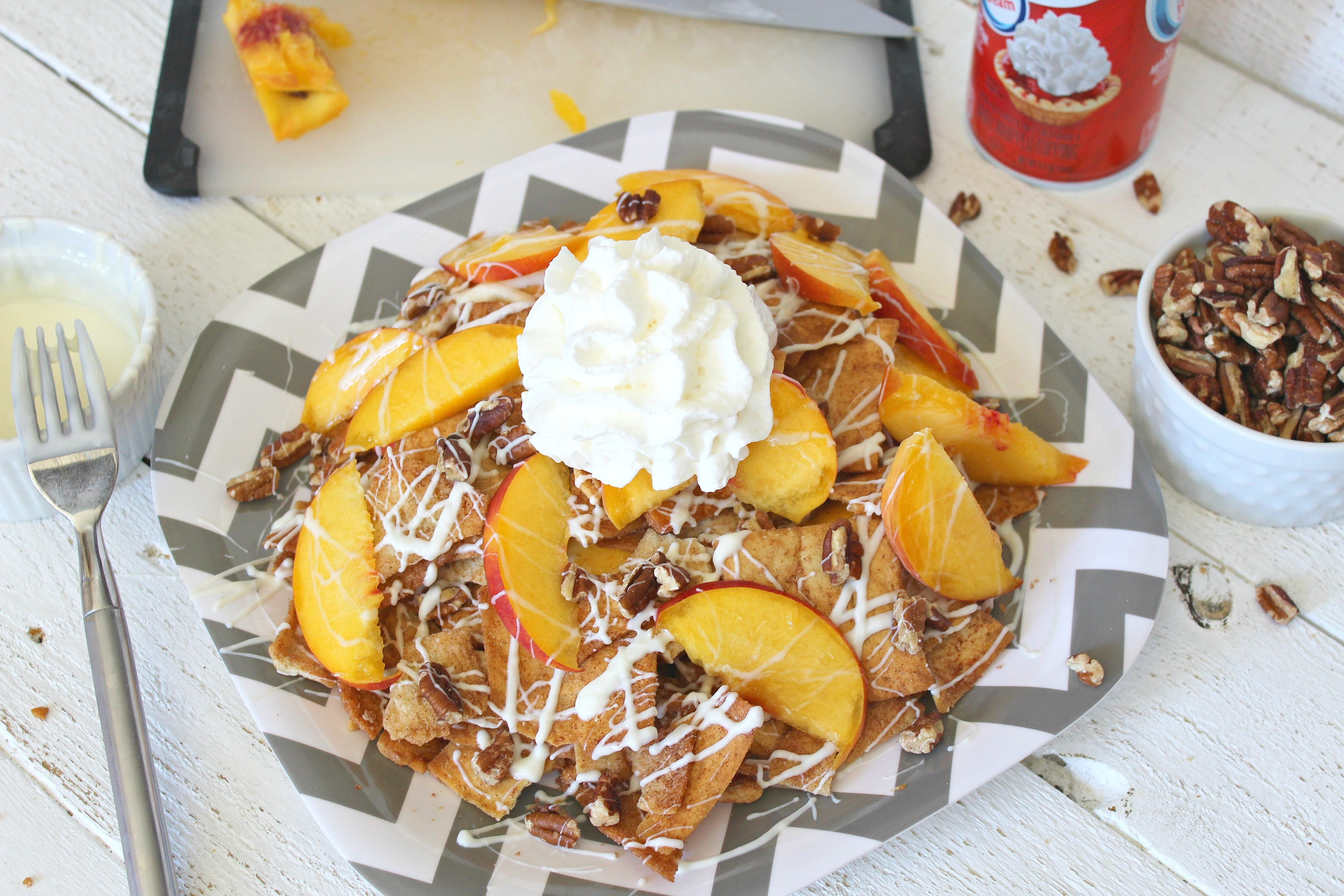 Top of the dessert nachos with whipped cream.