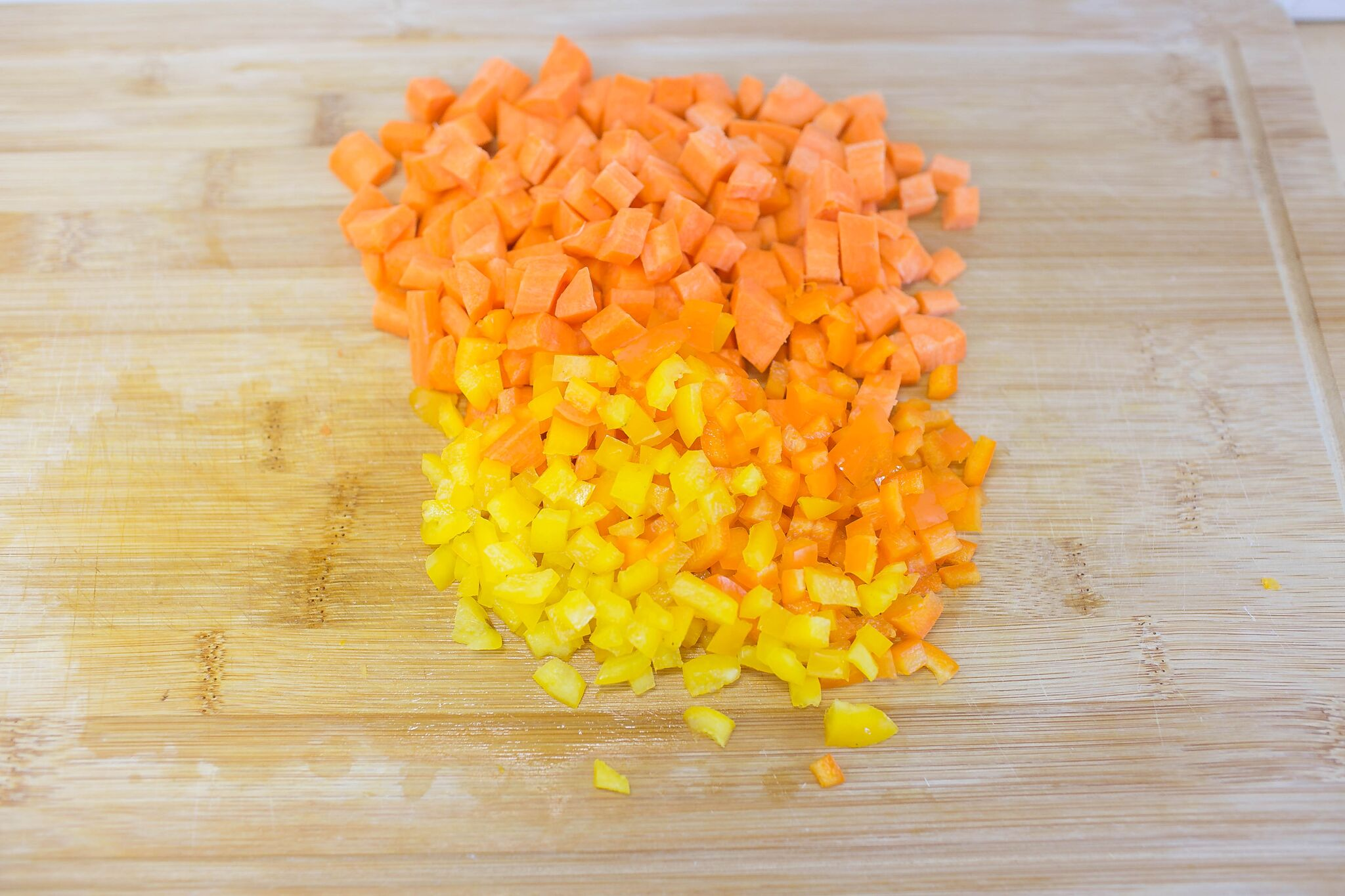 Dice carrots and peppers into bite sized pieces