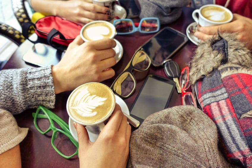 Friends enjoying beautifully made lattes with their phones, glasses and hats sitting on the table.