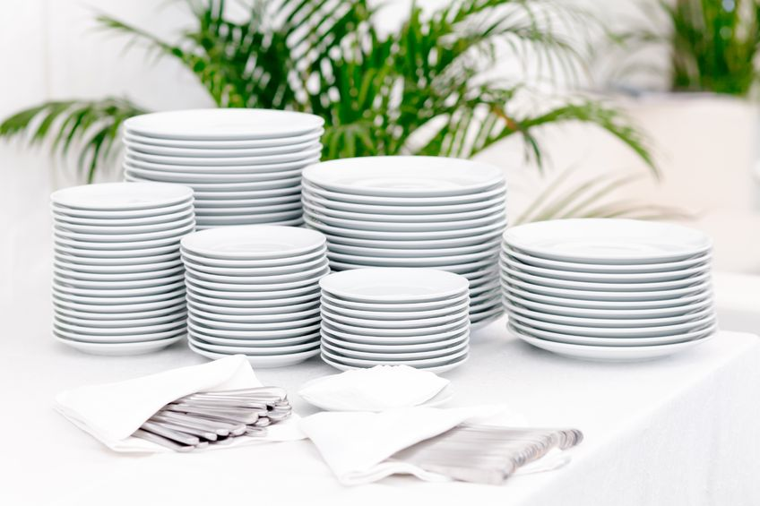 Clean white plates stacked and organized piles of utensils tucked in napkins.