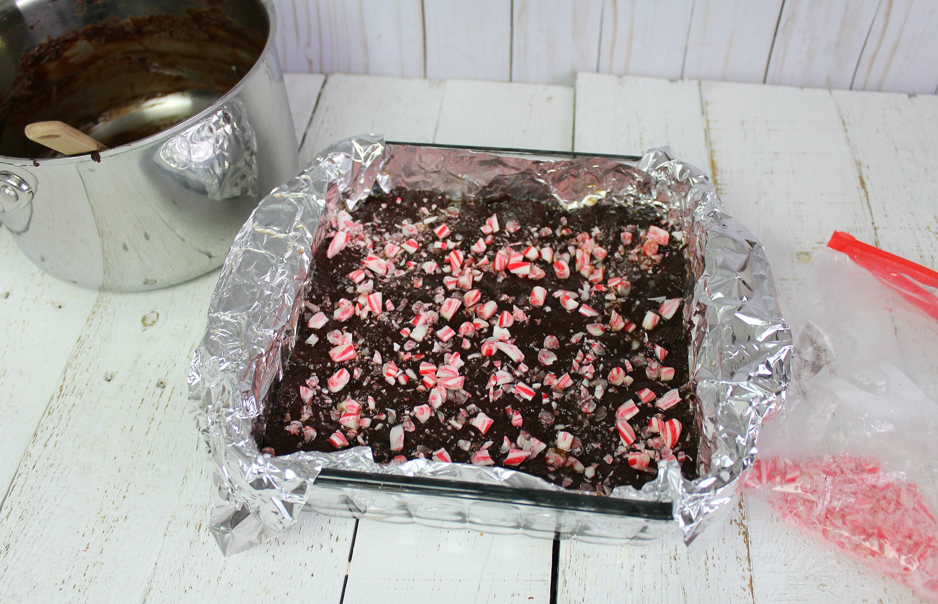 Step 5 of the Easy Peppermint Bark Fudge recipe is to spread the chocolate mixture to the prepared pan and sprinkle with crushed candy canes.