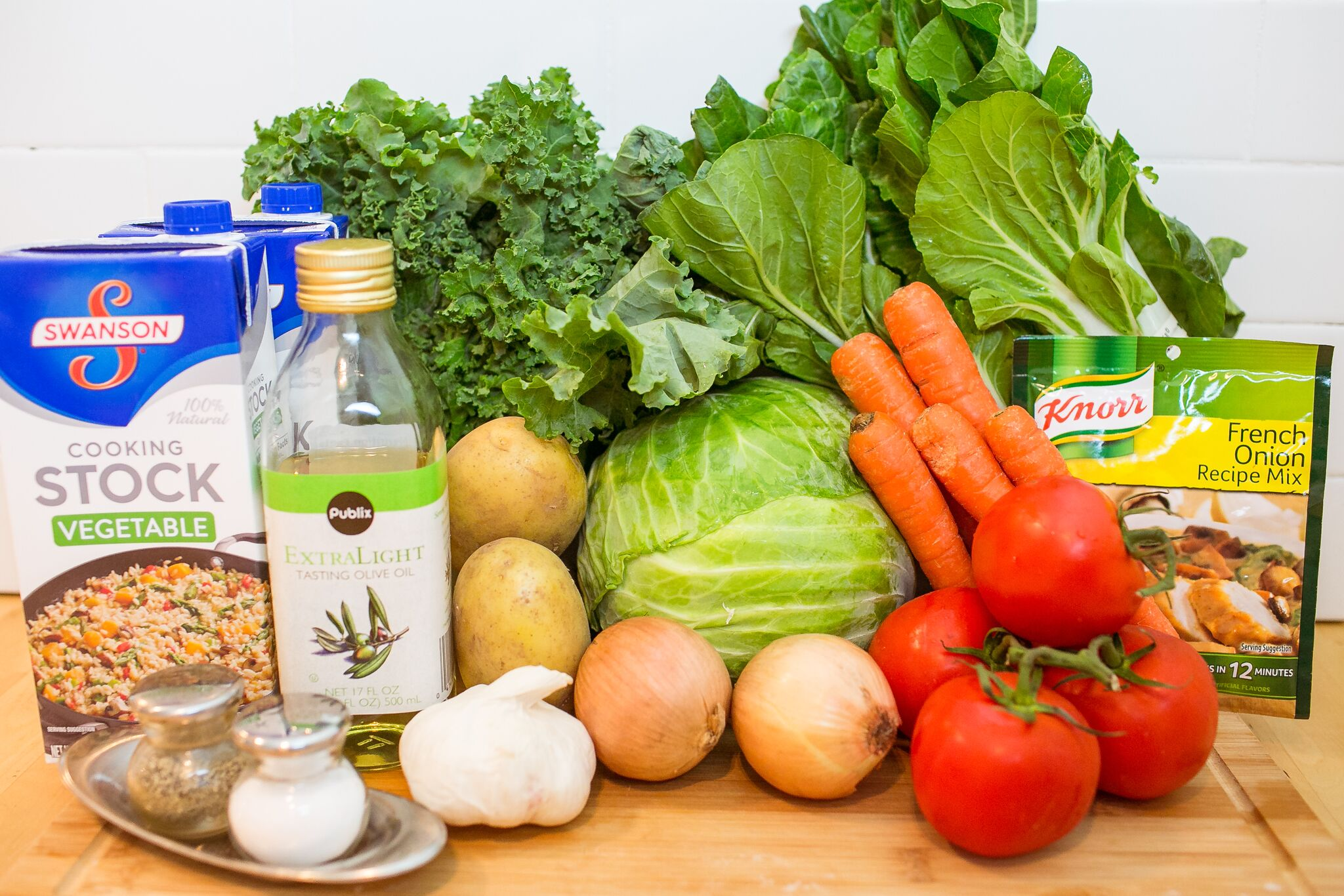 Assemble your ingredients for the winter diet soup: bok choy, kale, cabbage, olive oil, vegetable stock, tomatoes, yellow onions, garlic, salt, pepper, carrots, potatoes and french onion mix.