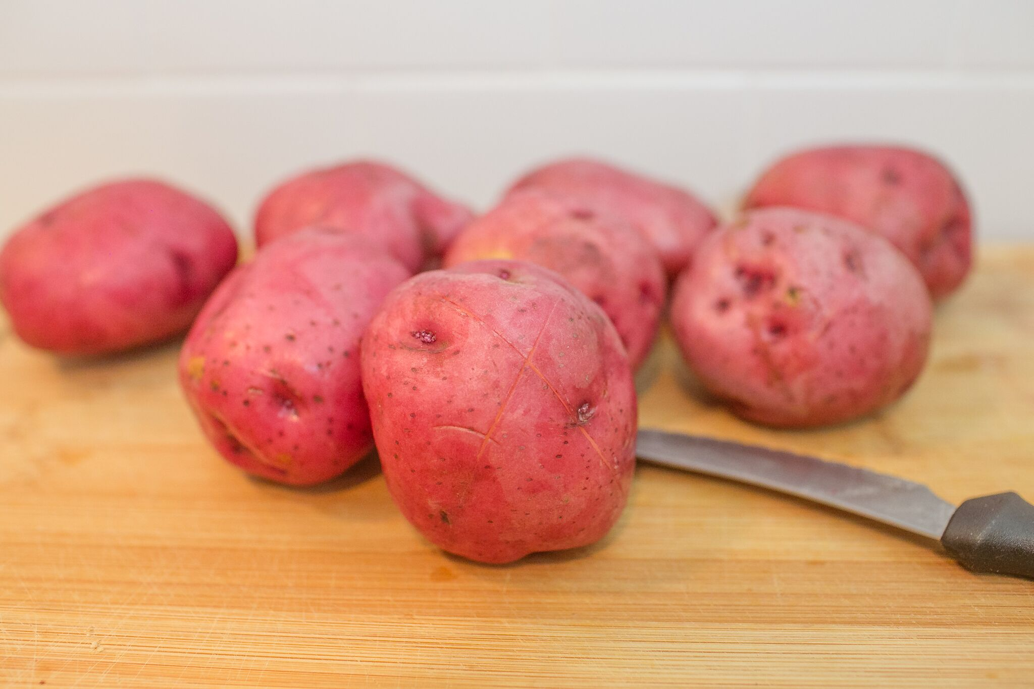 Wash the potatoes well and cut a small X into each one.