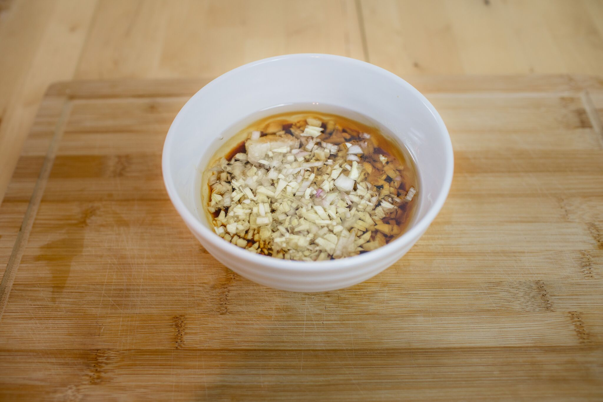 In a large bowl combine the fish sauce, soy sauce, sugar, pepper, sesame seed oil, vegetable oil, shallot and garlic.