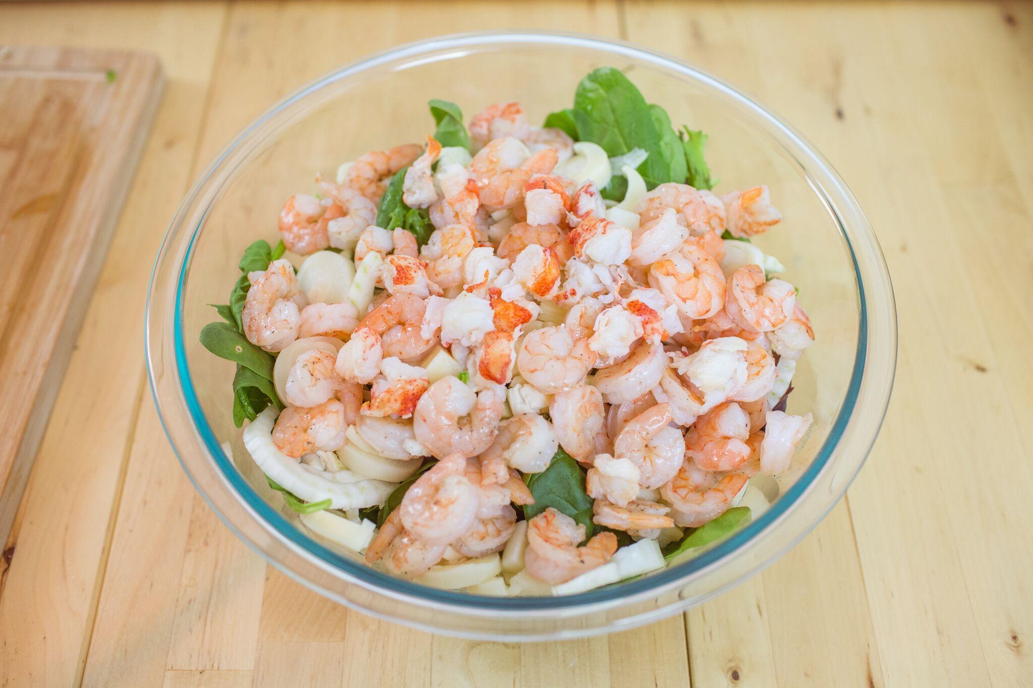 In a large bowl mix together, salad greens, sliced fennel, shrimp, lobster and add salad dressing.