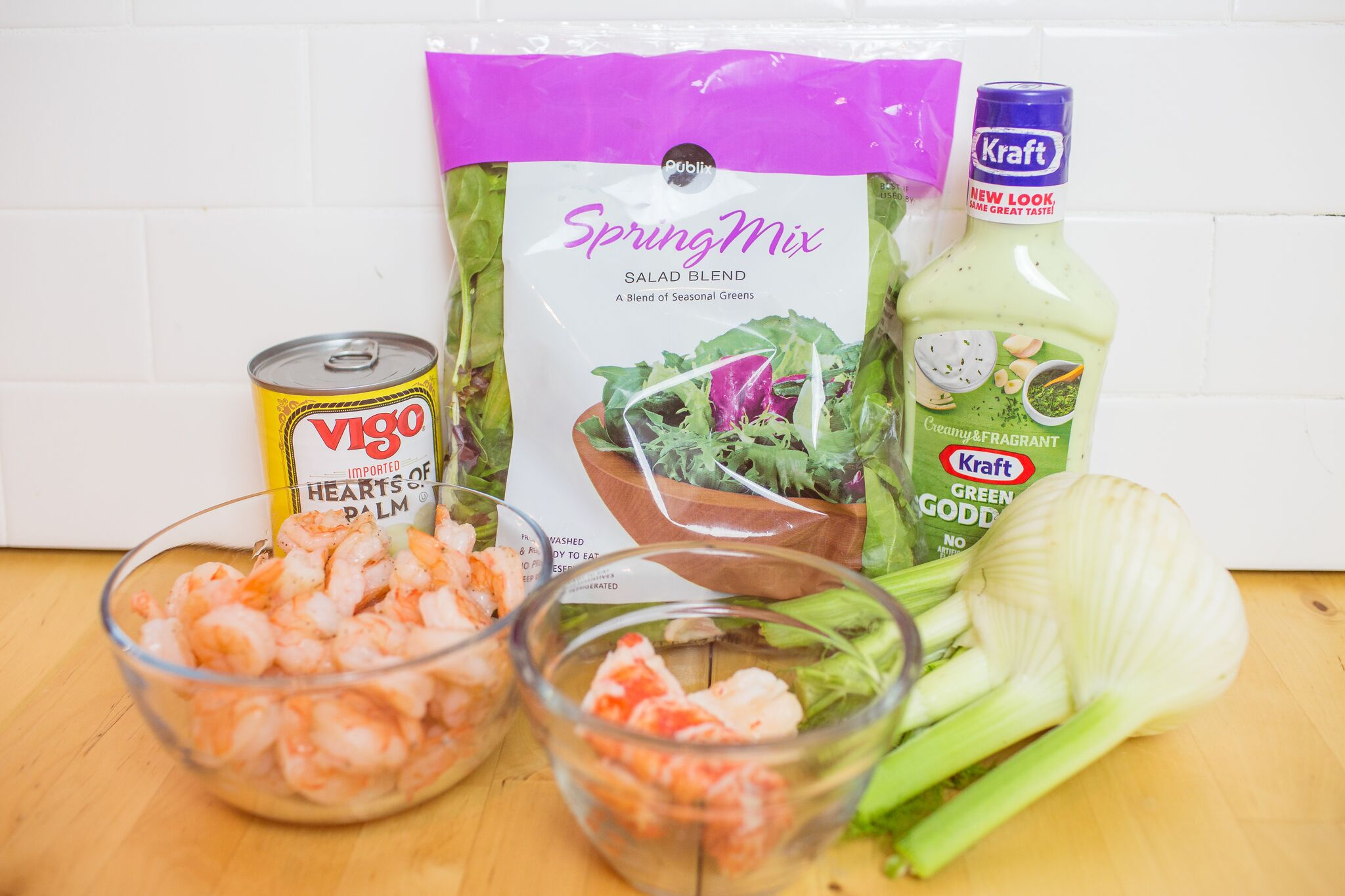 Assemble you fish salad ingredients: washed salad greens, fennel, hearts of palm, cooked shrimp, lobster tail and Green Goddess salad dressing.