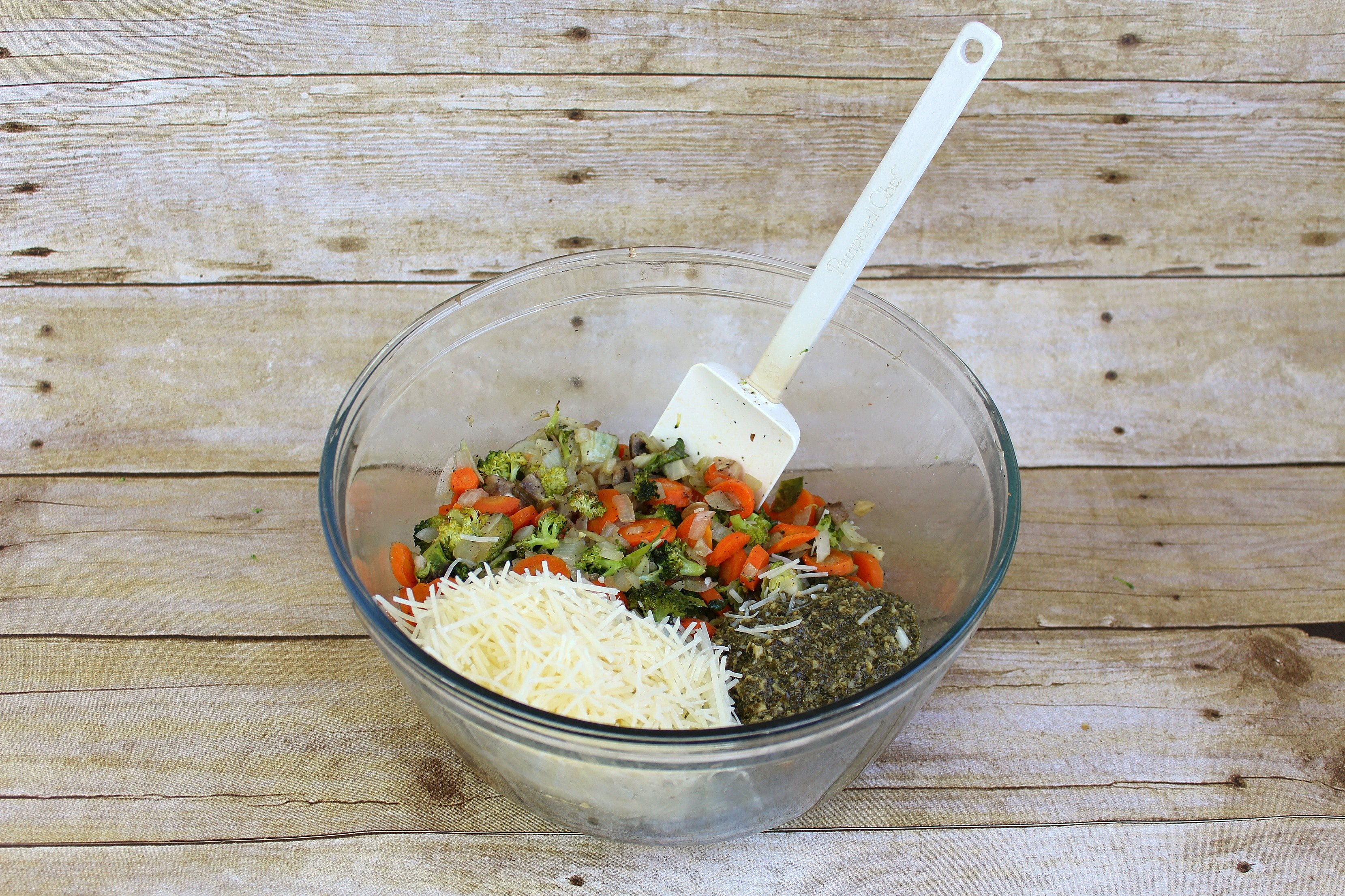 Add pesto and parmesan cheese into the roasted veggie mixture