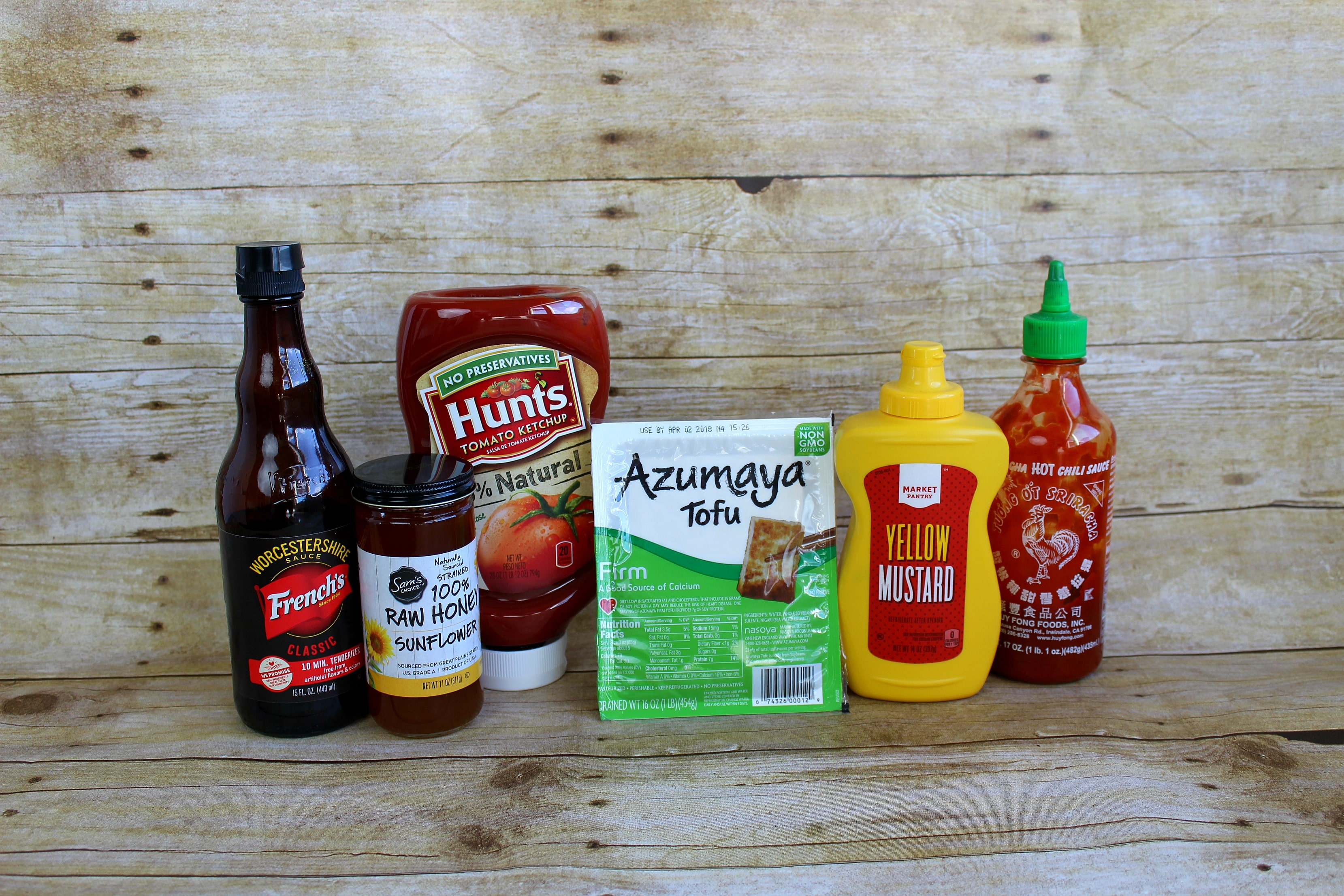 Assemble your ingredients for baked tofu: firm tofu, ketchup, yellow mustard, Worcestershire sauce, honey and Sriracha sauce.
