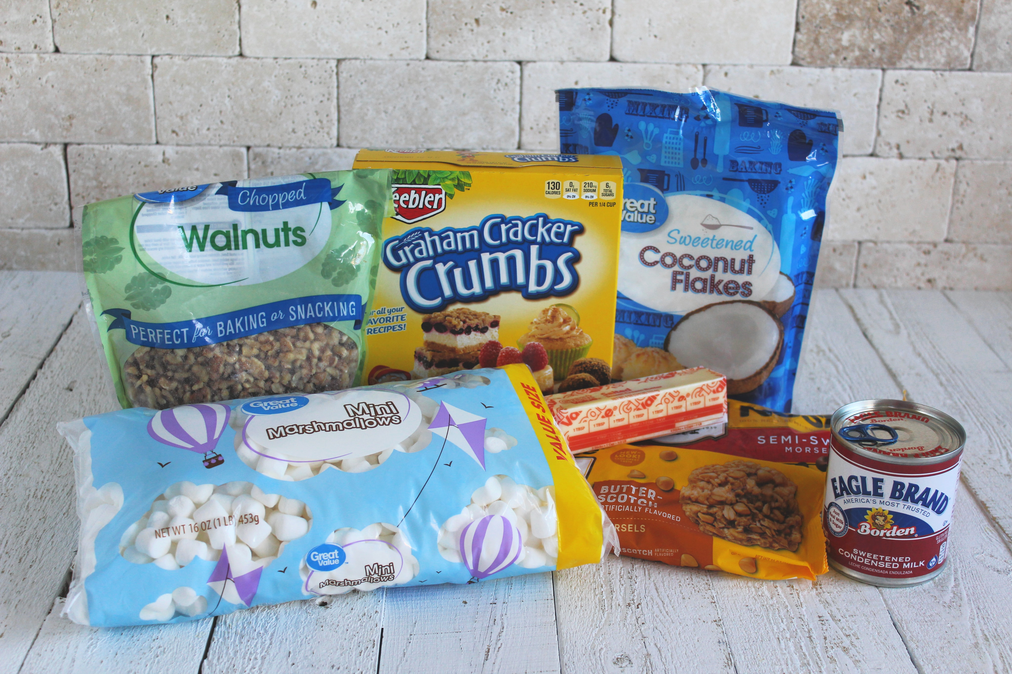 Assemble your ingredients for the 7-layer dream bars: graham cracker crumbs, butter, condensed milk, coconut, chocolate chips, butterscotch chips, mini marshmallows, and chopped pecans.