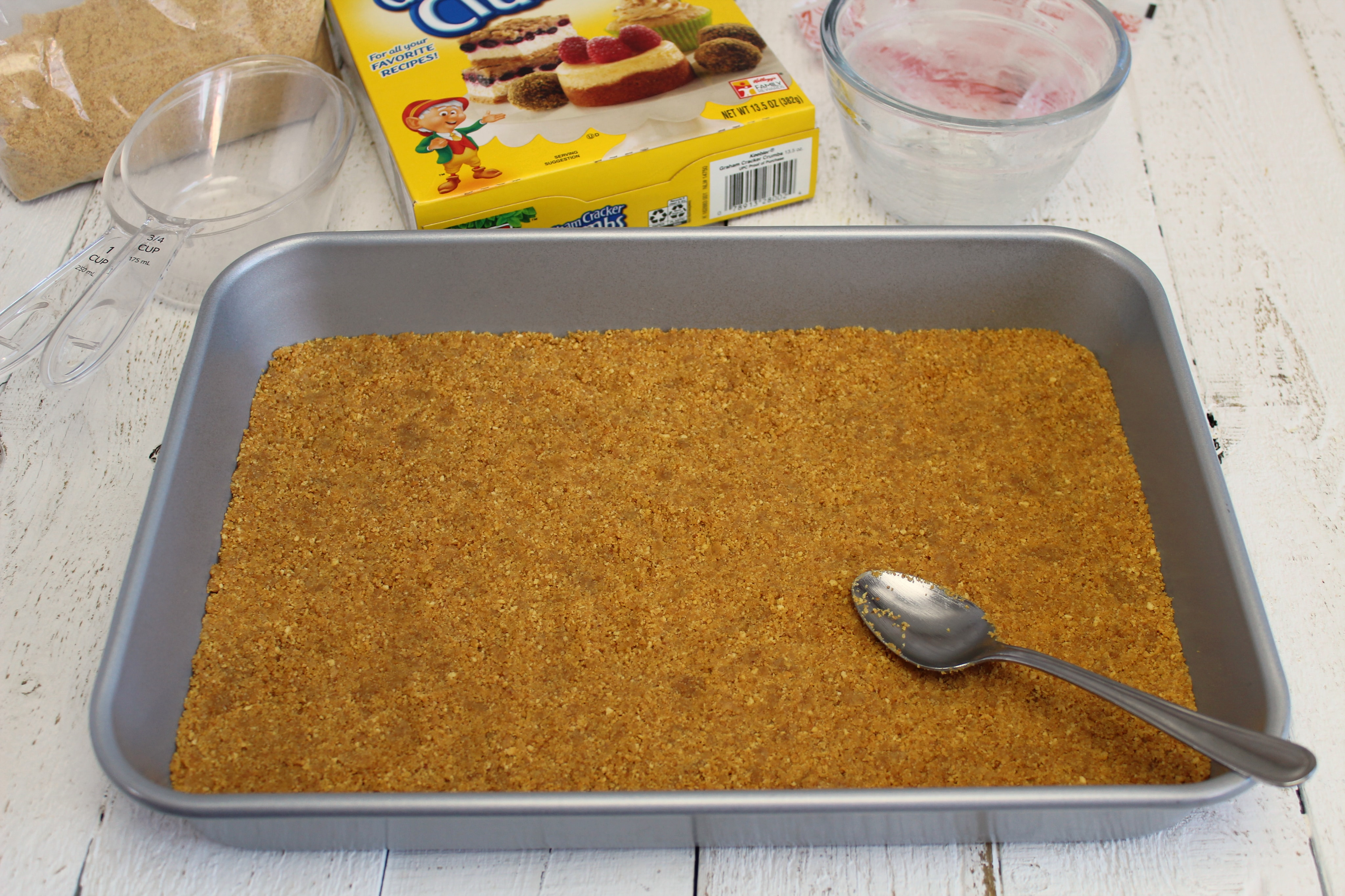 Spread graham cracker crumbs evenly on bottom of pan using a spoon.
