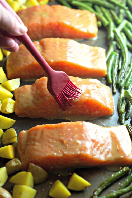 Brush salmon with Maple syrup and dijion mixture. Looking for a quick dinner recipe that uses just 5 ingredients? This Maple Glazed Sheet Pan Salmon with Potatoes and Green Beans is so easy and delicious! #recipes #easyrecipes #seafoodrecipes #onepanrecipes #5ingredientrecipes