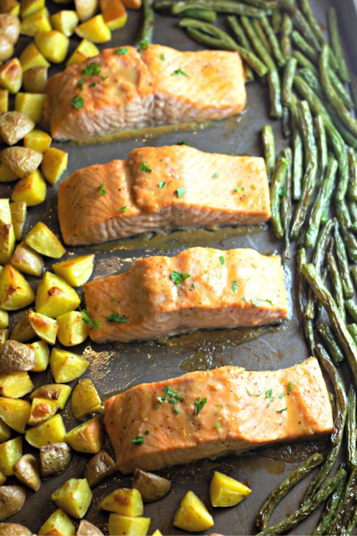 Finish slamon off in pan and then get ready to enjoy your one pot meal. Looking for a quick dinner recipe that uses just 5 ingredients? This Maple Glazed Sheet Pan Salmon with Potatoes and Green Beans is so easy and delicious! #recipes #easyrecipes #seafoodrecipes #onepanrecipes #5ingredientrecipes