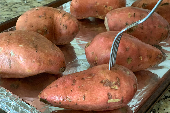 Step 1 fork potatoes before baking-A word of warning--once you've tried these incredible Twice Baked Sweet Potatoes, no other sweet potatoes will ever quite compare! They're not only utterly delicious (not to mention semi-addicting) and also a complete show-stopper for your Thanksgiving dinner. #recipes #thanksgivingrecipes #holidayrecipes #easyrecipes
